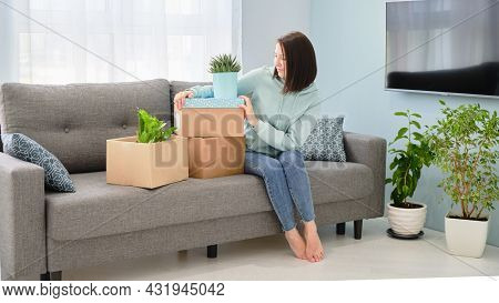 Woman Packing Or Unpacking Moving Home. Moving A Young Couple