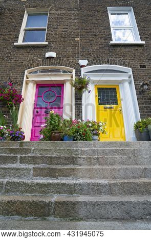 Steps Lead Upwards From Street To Bright Pink And Yellow Entrance Doors To Residential Apartments