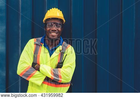 Young African American Male Worker At Overseas Shipping Container Yard . Logistics Supply Chain Mana