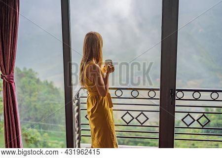 A Young Woman Holding Coffee Cup While Sittinhg On Chair On Balcony , Looking At Mountains And Green