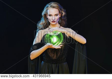 Magic on Halloween. Portrait of an enchanting young woman witch casting with an energy ball on a black background. Halloween make-up and costume.