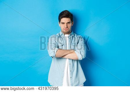 Angry Bearded Guy Crossing Arms On Chest, Frowning, Looking Mad And Offended, Standing Against Blue