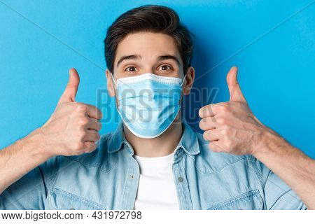 Concept Of Covid-19, Pandemic And Quarantine. Close-up Of Cheerful Young Man In Medical Mask Smiling