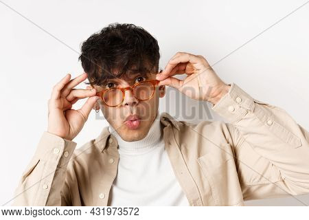 Close-up Of Attractive Young Man Checking Out Something Cool, Look Under Glasses And Saying Wow Amaz