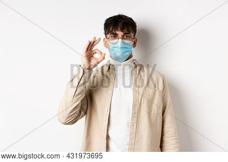 Covid-19, Health And Real People Concept. Natural Guy In Glasses And Medical Mask Show Ok Sign, Agre