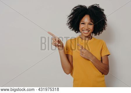 Look Here. Studio Portrait Of Beautiful Cheerful Dark Skinned Woman Dressed In Yellow Tshirt Pointin