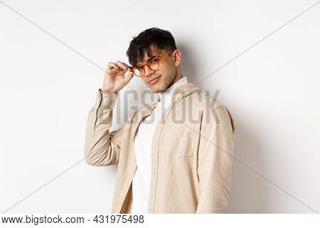 Handsome Stylish Guy Saluting You, Touching Eyewear And Smiling Sassy, Standing On White Background