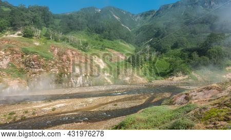The River Flows Along A Rocky Bed. The Water Is Foaming. There Is Green Vegetation On The Mountain S