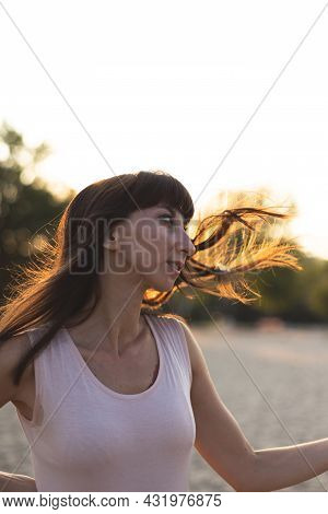 A Young Girl Shakes Her Head With Her Hair Tousled In The Wind. A Beautiful Girl With Dark Hair Flut