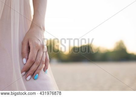 Girl's Hand With Beautiful Manicure Holds A Summer Dress