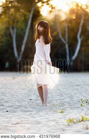 Beautiful Young Fashionable Woman In Elegant Dress Walking At The Beach At Sunset