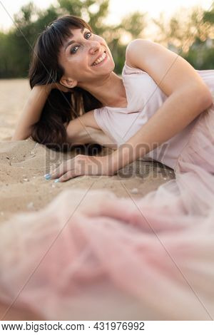 A Young And Happy Girl In A Light Dress Lies On The Sand. Joy And Fun
