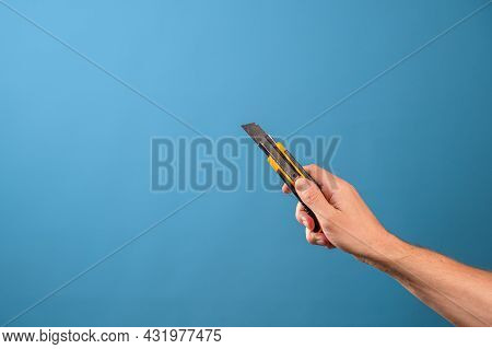 Cut Or Shorten Something, Cut It Out. A Mans Hand Holds A Stationery Knife