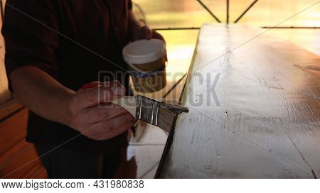 Manual Application Of A Protective And Decorative Lacquer Coating On A Textured Wooden Bench, Glossy