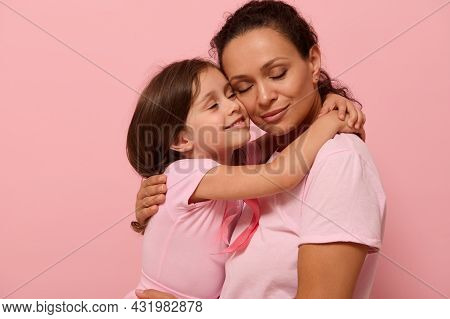 Beautiful Loving Mother And Daughter, Hugging Each Other, Wearing Pink Clothes With A Pink Ribbon, S
