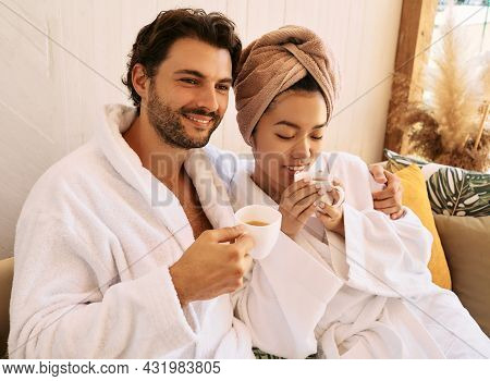 Loving Young Couple In White Bathrobes Spending A Weekend At A Spa And Enjoying Wellness Tea. Resort