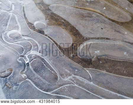 Round Irregular Shapes In Ice On Frozen Puddle In Winter, Concept Of Rigidity And Stillness