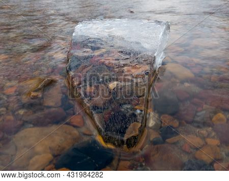Translucent Angular Clean Piece Of Ice In Running Water With Colorful Stones Underneath In Winter, R