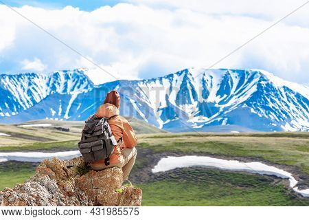 Mountain Climber Man Or Tourist Man With A Backpack On The Top Of The Mountain Sits And Looks At The