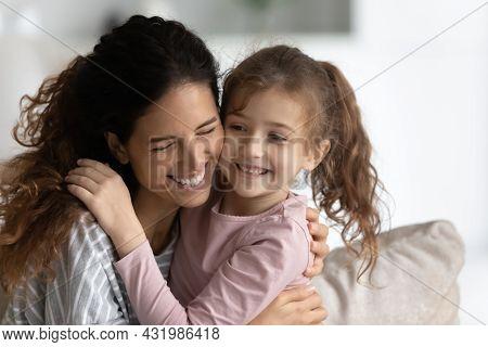 Sincere Millennial Hispanic Woman Cuddling Cute Small Kid.