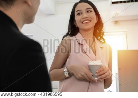Coffee Break. Couple Of Colleagues Young Asian Business People In Smart Casual Relaxing And Holding