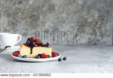 Slice Of Cheesecake With Chocolate Sauce, Berries And A Cup Of Coffee On The Kitchen Table, On A Con