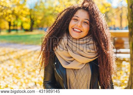 Attractive Afro-haired Woman With Snow-white Smile Wearing Warm Scarf Walk In Autumn Park At Sunny W