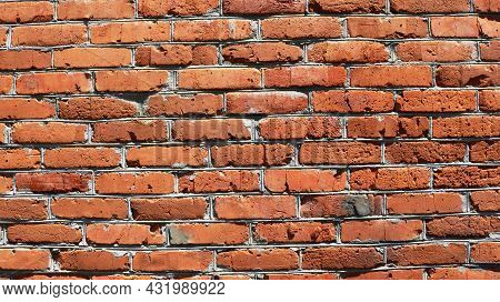 Fragment Of Uneven Street Brick Wall Detailed In Bright Sunlight, Design Background Of Aged Brick Sh