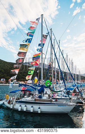Agia Efimia, Cephalonia Island, Greece - July, 12 2019: Small White Yachts With Many Multicolored Fl