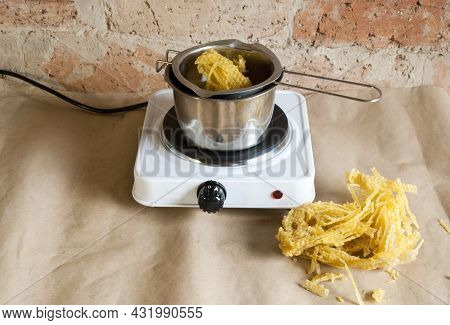 Raw Beeswax For Making Large Candles. Homemade Candle Making.beeswax In The Process Of Melting Into