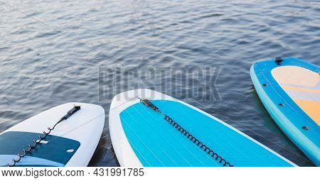 Surf Boards On Blue Clean Water Surface Background. Surfing And Sup Boarding Equipment In Sunset Lig