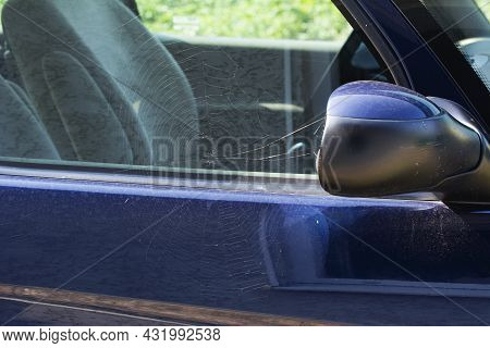 Big Spider Web On Automobile Door And Mirror. Minimal Abandoned Or Left Car, Car Cemetery Concept