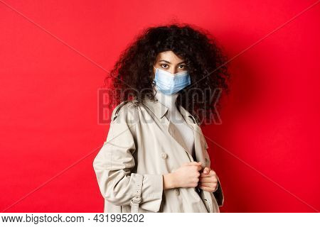 Covid-19, Pandemic And Quarantine Concept. Sassy Girl In Trench Coat And Medical Mask, Put On Trench