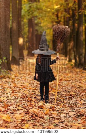 Cute Happy Little Redhaired Girl Dressed In Witch Costume Standing With Broom Over Autumn Forest Bac