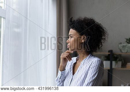Contemplative Young Black Businesswoman Look At Window Touch Chin Thinking