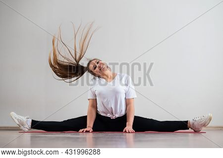 A Young Flexible Fat Woman Sits In A Transverse Twine And Waves Her Hair Against A White Background