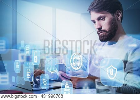 Businessman Wearing White Pullover Is Working On Laptop With Hologram Of Globe, Coin, Padlock, Cloud