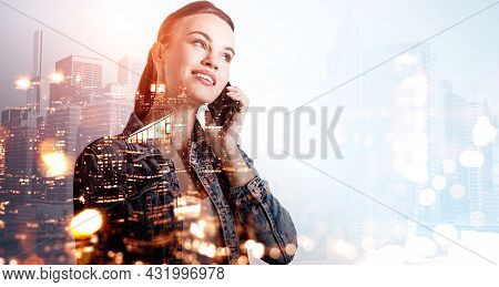 Businesswoman Wearing Jeans Jacket Is Talking On Smartphone. Singapore And New York City Financial D