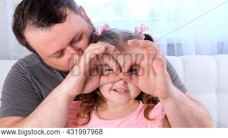 Little Daughter 3 Years Old And Father Are Having Fun At Home, Making Funny Faces, Making Glasses Wi