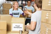 Volunteers Collecting Food Donations In Warehouse poster
