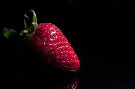 Strawberry single with drops isolated on black