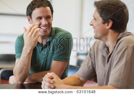 Two friendly male mature students chatting while sitting in class room