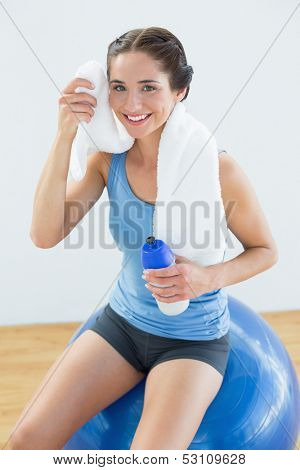 Portrait of a smiling young woman with towel around neck and waterbottle sitting on exercise ball