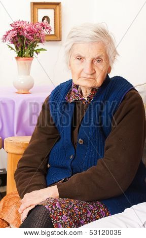 Elderly Lonely Woman Sits On The Bed