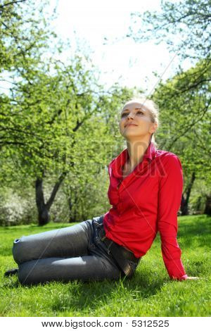 Beautiful Blonde Sits On Grass And Looks Upward In Garden In Spr