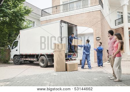 Young couple watching movers move boxes from the moving van