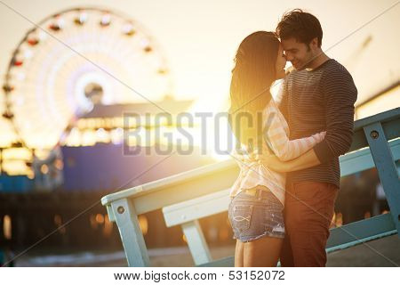 romantic couple kissing at sunset in fromt of santa monica ferris wheel.
