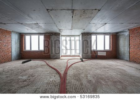 Empty room with a rough finish and several radiators