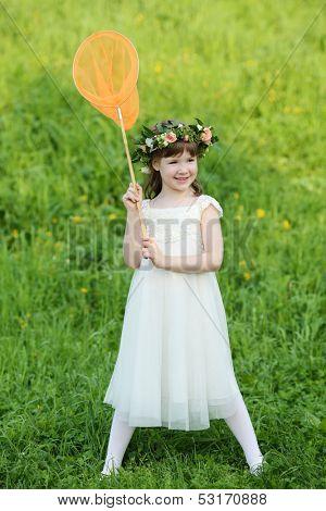 Little cute girl in white holds orange butterfly net on green meadow.