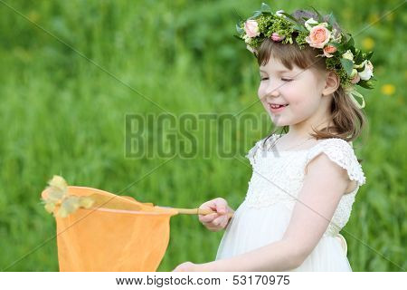 Little cute girl in white looks at butterfly sitting at net on green meadow.